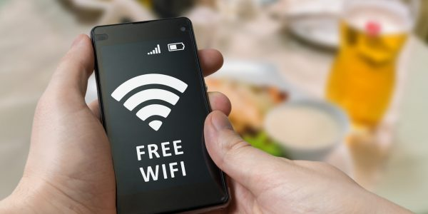 Man holds smartphone and is using free wifi in restaurant.