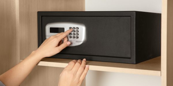 Woman opening black steel safe with electronic lock at hotel, closeup